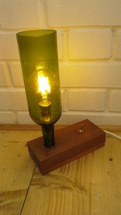 Hi here is a wine bottle light. It has been made from an upside down wine bottle with the bottom cut off and set in a piece of mahogany and ash. The light is a standard BC bulb holder with an LED string bulb and the switch is a retro arrow toggle switch. Size H 30cm X W 8cm X L 19cm