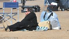 A day at the seaside: Tom chilled out on a towel and caught some rays while he waited to f...