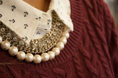 Patterned collar peeking out from a knit sweater. Complete with a rhinestone and pearl necklace.