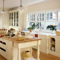 English Lessons             Because the kitchen is open to the dining and living rooms, the homeowners chose a formal look that features painted cabinetry with inset drawers, beaded details, and glass knobs. At the far end, a built-in hutch holds dishware opposite the breakfast table
