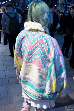 oversized coat with pastel ethnic-inspired designs and pastel braids/tassels, faux fur collar.