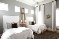 Dodson  Daughter ID    Chic, sophisticated girls' bedroom with gray walls paint, white curtains window panels, arched windows, blue  brown geometric pattern rug, driftwood sol mirror, white twin slipcover beds, blue gray metallic pillows and chocolate brown flower pillows.