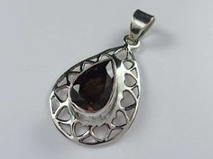 Elegant and patterned sterling silver pendant with cut smoky quartz stone and fine details throughout.