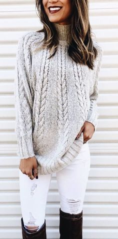 Gray cable knit sweater with white distressed jeans and black OTK boots.