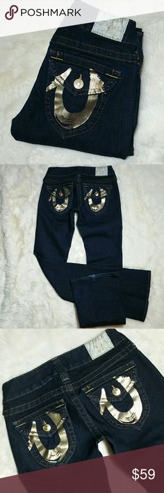 """True Religion Joey Gold Horseshoe Stretch Jeans 26 True Religion Joey Gold Horseshoe Stretch Jeans Size 26. Inky dark blue wash. Flap button pockets with gold painted horseshoes & finished off with gold hardware and gold stitched waistband logo. Button and zip fly. A tri blend of 88% cotton, 10% polyester and 2% spandex makes for a very stretchy denim. Some hemwear as photographed but with the long inseam of 34"""", hem wear can be eliminated entirely if altered. Preowned in great condition…"""