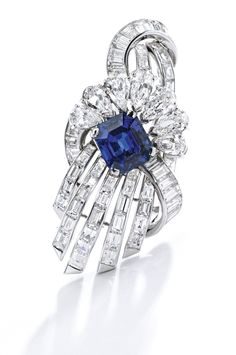 Platinum, Sapphire and Diamond Brooch, Harry Winston The stylized floral spray set with an emerald-cut sapphire weighing 7.66 carats, accented by baguette, tapered baguette and pear-shaped diamonds weighing approximately 11.25 carats, signed Winston.