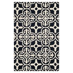 Stylishly anchor your living room or master suite with this elegant hand-tufted wool rug, showcasing an ornate quatrefoil motif in black and ivory.