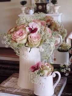 Pink roses, pansies, and Queen Anne's lace in white pitchers