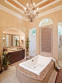 This master bathroom features gold walls, mosaic tile accents and stone finishes. A romantic chandelier illuminates the beautiful tray ceiling while a deep white tub sits below for a luxurious, relaxing spot.