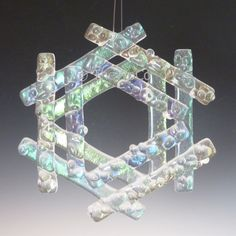 Fused iridized clear glass snowflake with crystalline detail, developed and formed by me, and arrives in its own decorative keepsake gift box. Ready to hang as an ornament or sun catcher from clear floss. Each Snowflake Sold Separately. Like real snowflakes, no two are alike! Each iridized