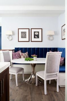 Chic dining room boasts a L shaped dining banquette upholstered in sapphire blue velvet fabric facing a round marble and hammered metal dining table lined with gray French square back chairs illuminated by Chart House Large Ring Sconces.