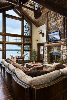 Love the stone wall fireplace and the wonderful sofa sectional style in this terrific living room with a view!