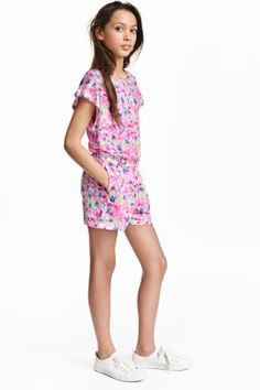 Playsuit: Playsuit in soft jersey with short cap sleeves, an opening with a button at the back of the neck, an elasticated seam at the waist, side pockets and short legs.