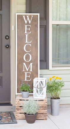 "Wooden ""Welcome"" Sign and Metal Potted Plants"