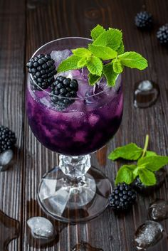 44183331 - tasty blackberry cocktail in wine glass with mint and ice on dark wooden table. summer berry lemonade
