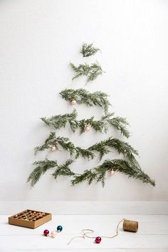 a minimalist wall mounted Christmas tree of evergreens and little copper ornaments on them for an airy feel Wall Christmas Tree, Creative Christmas Trees, Christmas Tree Design, Holiday Tree, Christmas Tree Decorations, Christmas Tree Ideas For Small Spaces, Winter Holiday, Minimalist Christmas, Modern Christmas