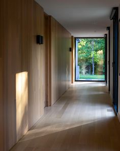 Views of the trees can bee seen through the black-framed windows that line the hallway to the bedrooms.