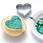 potato stamp  Spread the luck o' the Irish this St. Patrick's Day with a homemade shamrock stamp. Use it to decorate paper place mats, coasters, tablecloths, or anything else your little leprechauns wish to dress in green.    Materials  Heart-shaped cookie cutter (2 1/2 inches wide and long)   Potato, cut in half   Paring knife   Green acrylic paint   Paintbrush   X     Instructions  1. Press a heart-shaped cookie cutter (ours was 2 1/2 inches wide and long) into the cut face of a potato…