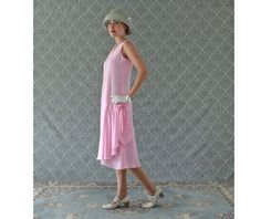 This pink 1920s-inspired flapper outfit is sweet, feminine and really stylish. It is made of pink chiffon fabric, which is very light and soft to the touch. A perfect dress for your next 1920s-themed party or spring/summer wedding. The design is loose fitting, sleeveless with a drop-waist and a v-neckline. Two diagonal panels of the front of the skirt cross in the middle, making the sides slightly longer than the middle. One side of the panel continues to form beautiful drapes on the sid...