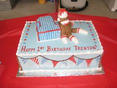 birthday cake, find figurine for the sock monkey ppart? make banner on cake and wall match...