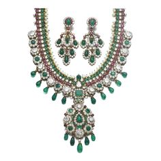 Comprising: a necklace of Indian inspiration, set with variously shaped emeralds and rubies, seed pearls, drop-shaped and a carved emerald, circular-cut, cushion-shaped and a pear-shaped diamond, supporting a detachable pendant set with a cabochon pear-shaped emerald, circular-cut rubies, similarly cut, cushion- and drop-shaped emeralds, circular-cut and cushion-shaped diamonds, may be worn as a brooch, necklace length approximately 490mm, French maker's mark for Van Cleef & Arpels