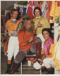 Farrah Fawcett making a celebrity appearance at the now closed Hollywood Park horse race track poses with jockeys, Willie Shoemaker, Sandy Hawley, Laffit Pincay - 1975