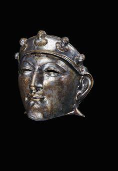 Esta máscara de hierro chapada en bronce y plata, descubierta en los Países Bajos, estaba unida al yelmo de un soldado mediante una bisagra. Se portaba en desfiles y quizás en la batalla