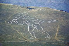 The Cerne Abbas Giant is a hill figure near the village of Cerne Abbas in Dorset, England. Made by a turf-cut outline filled with chalk, it depicts a large, naked man, with a substantial erect penis, typically described as a giant, wielding a club. The figure is listed as a scheduled monument in the United Kingdom and the site where he stands is owned by the National Trust.
