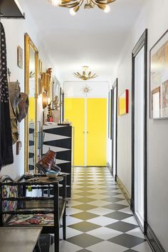 Colorful and long entryway with a checkerboard linoleum floor and elegant details.