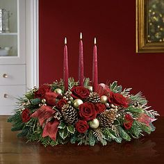 Miniature carnations are artfully on display with merry touches like shimmery ornaments, pinecones, berries, organza ribbon and holiday greens. Three graceful red taper candles add the perfect magical touch. Christmas Candle Decorations, Christmas Flower Arrangements, Holiday Centerpieces, Christmas Flowers, Christmas Wreaths, Christmas Crafts, Christmas Ornaments, Christmas Ideas, Holiday Decor