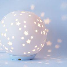 ¡Una lamparita decorativa muy original! Con forma de bola y estrellitas perforadas que dejan pasar la luz, acabada en porcelana blanca.