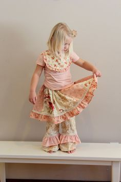 A darling patchwork skirt made up of vintage looking prints of pinks, tans and and peaches. This skirt has lots of twirl and is completed with a ruffle on the bottom and trimmed with lace.