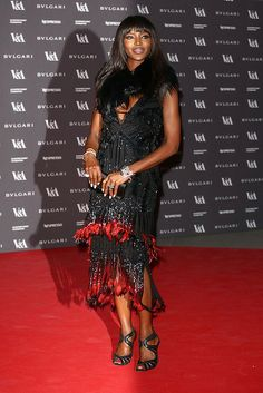 This dress is probably worth a lot of money but it looks cheap & nasty and does she really need the fluff around her neck? Naomi Campbell at the The Glamour Of Italian Fashion opening.