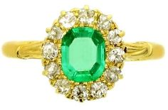 Antique emerald and diamond cluster ring, circa 1900. A yellow gold ring set with one central rectangular emerald-cut emerald in a bead setting with an approximate weight of 0.60 carats, encircled by a single row of twelve round old cut diamonds in claw settings with an approximate total weight of 0.50 carats, flanked by shoulders carved with scrolled decoration, and on tapered half round shank. Berganza.
