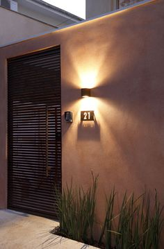 EXTERIOR LIGHTING (SHINES UP AND DOWN) GRAZING THE BRICKWORK. STAINLESS STEEL NUMBERS ON THE RIGHT SIDE OF FRONT DOOR (UNDER THE FIXTURE).