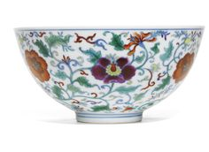A DOUCAI 'FLORAL' BOWL YONGZHENG MARK AND PERIOD the deep rounded sides rising from a short straight foot to an everted rim, brightly decorated around the exterior with composite large flower heads borne on leafy scrolling tendrils, the interior with a similarly decorated medallion, the base with six-character mark in underglaze-blue, wood stand
