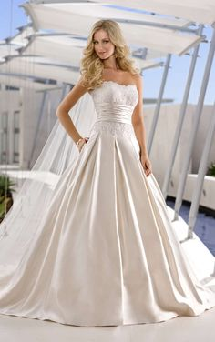 Stella York - This rich Dolce Satin designer wedding gown has a delicate Lace bodice with a highly-fashionable ruched band at the waist. The ballgown skirt is features box-pleats at the waist and is accented with side pocket detail.