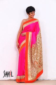 Pink and golden satin georgette saree featuring a golden net palla with gold zari embroidery. It has an orange and golden china silk border with a golden edging. The saree comes with an unstitched blouse piece.
