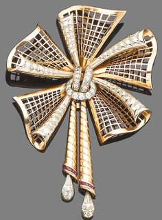 A diamond and synthetic ruby bow brooch, circa 1940.  The openwork lattice decorated with old brilliant and single-cut diamonds, terminating in engraved tassels with calibré-cut synthetic ruby and single-cut diamond highlights, length 8.9cm.