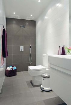 The dark wall and continued floor with white walls makes a great wet bathroom
