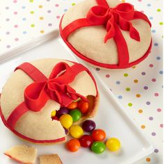 The shells are formed by inverting sugar cookies made in a Whoopie Pie Pan. Topped with a big red bow and filled with anything you'd like.