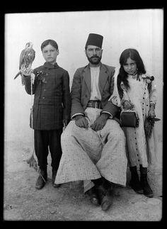 En Syrie, près de Palmyre, le maire du village de Qariateïn avec son fils, et sa fille, chacun des enfants tenant un objet symbolique de la ...