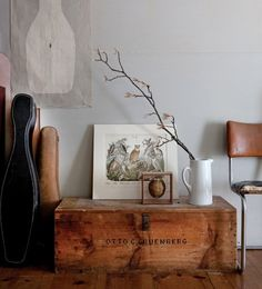 I need to need to find and antique trunk like that. No metal, light wood, some writing, it's perfect. I love the vintage instrument cases next to it, and the simple branch in a vase to add life. #myloft #antiquestofind #designwithnature