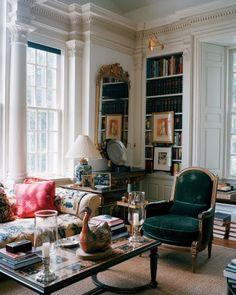 Living room with antiques, green velvet, blue and white lamp, candle sconces, books - Oscar de la Renta