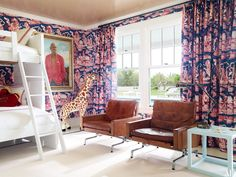 A Quadrille toile fabric and wallpaper envelop one of the children's rooms in a Southampton, New York, beach house decorated by David Netto. The furnishings include a Room & Board bunk bed, vintage Poul Kjærholm armchairs from Dansk Møbelkunst Gallery, and a Stark carpet; the portrait is of one of the homeowners' grandfathers.