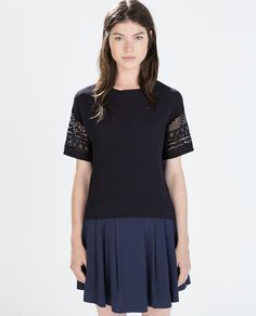 We saw lots of lace trims.  This is a crochet-like sleeve on a textured woven boxy shape top.