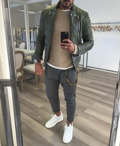 Pairing an olive leather moto jacket with grey pants is a comfortable option for running errands in the city. Round off this look with white low top sneakers.   Shop this look on Lookastic: https://lookastic.com/men/looks/biker-jacket-crew-neck-sweater-crew-neck-t-shirt/20090   — White Crew-neck T-shirt  — Tan Crew-neck Sweater  — Olive Leather Biker Jacket  — Dark Brown Leather Watch  — Grey Chinos  — White Low Top Sneakers