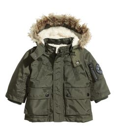 Parka in woven fabric with detachable hood with detachable faux fur trim. Zip and windflap at front with Velcro fastener. Front pockets with snap fasteners, one sleeve pocket with zip, decorative handwarmer pockets, and inner ribbing at cuffs. Lined.