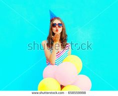 Beautiful young woman in a birthday cap is sends an air kiss holds an air colorful balloons on a blue background
