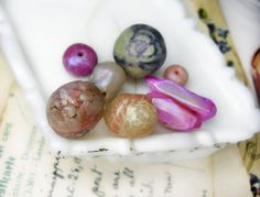 8 polymer clay beads -Shapes are organic, nuggety rounds/rondelles, briolette points -Embellishments and features include: paint, glitter,